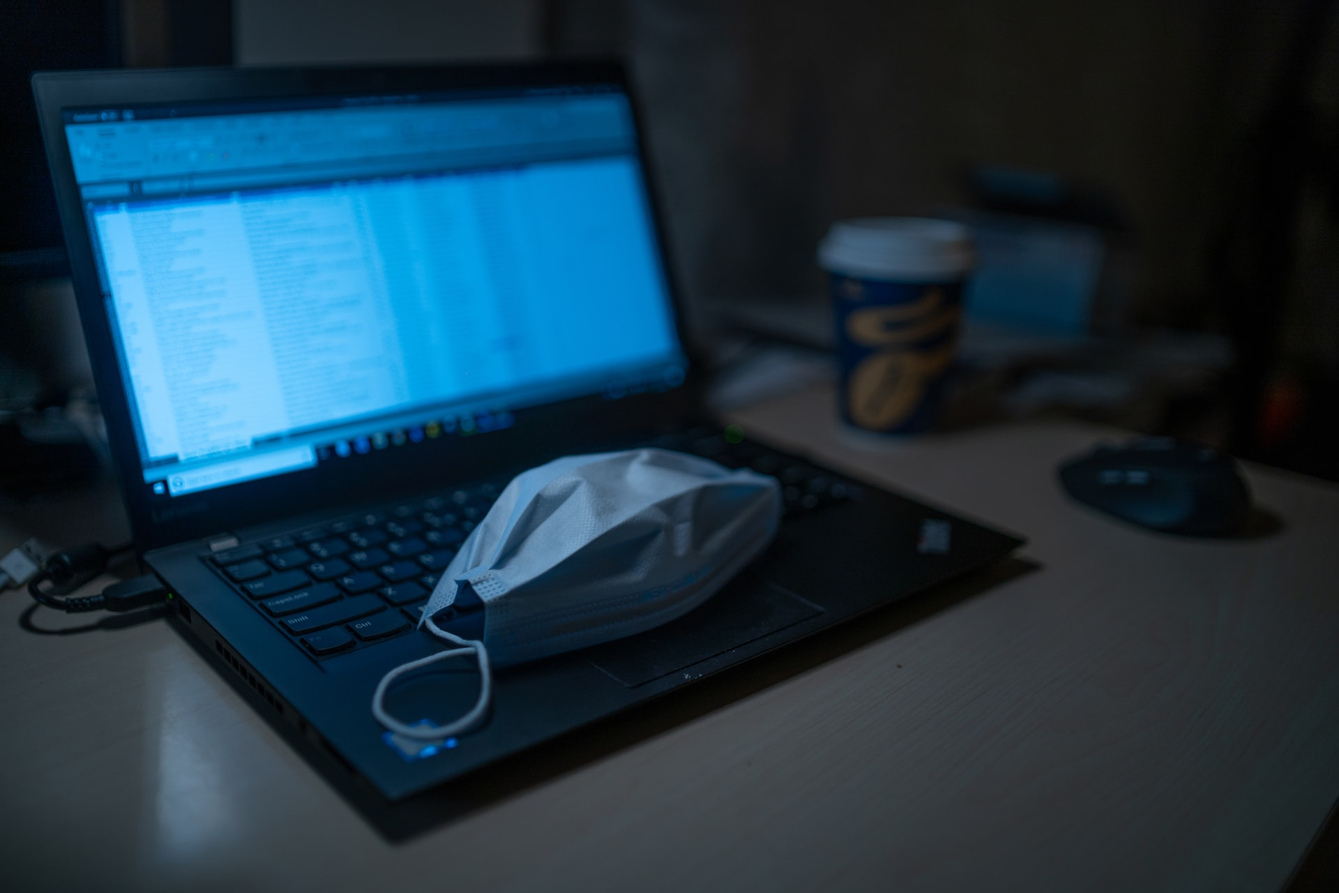 Laptop and a white protective mask representing the pandemic
